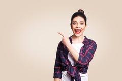 有便装样式和小圆面包头发的年轻愉快的女孩指向她的手指的斜向一边,展示某事在米黄死墙上 免版税库存照片