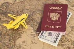 有俄国国际护照和美元的模型飞机 免版税库存图片