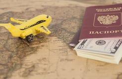 有俄国国际护照和美元的模型飞机 免版税库存照片