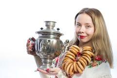 有俄国式茶炊和面包圆环的美丽的白俄罗斯语的白肤金发的妇女 免版税库存照片