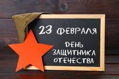 有俄国文本的黑板:祖国保卫者日2月23日, 库存图片