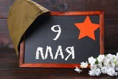 有俄国文本的黑板:5月9日 40争斗已经来然而荣誉称号比那里更放置内存纪念碑在通过的爱国人位置可能的战士对未知的退伍军人胜利战争几年的日永恒法西斯主义花荣耀了不起的英雄 俄国假日 免版税库存照片
