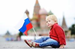 有俄国旗子的逗人喜爱的男孩与在背景的红场和Vasilevsky下降 免版税图库摄影