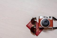 有俄罗斯联邦的公民的护照和一台立即照片照相机的太阳镜在白色木背景 库存照片