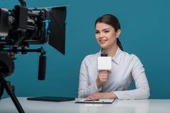 有俏丽的微笑的美丽的女孩电视新闻广播员 免版税库存照片