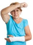 有保护自己的一条断胳膊的年长妇女 免版税库存照片