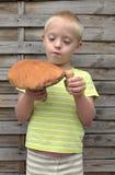 有保持向下使两个橙色蘑菇的综合症状的男孩 免版税库存图片