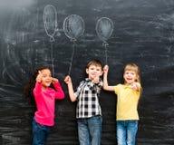 有保持imaginaru的赞许的三个微笑的孩子被画迅速增加 免版税图库摄影