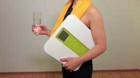 有保留杯水和标度的黄色毛巾的妇女 股票视频