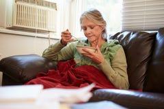 有保留温暖的下面毯子的贫寒饮食的资深妇女 免版税库存照片