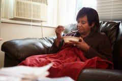 有保留温暖的下面毯子的贫寒饮食的资深妇女 免版税图库摄影