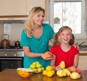 有保留的甜梨女儿微笑的母亲 健康吃-妇女和孩子在用不同的种类的厨房里果子 免版税库存图片