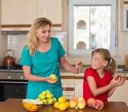 有保留的甜梨女儿微笑的母亲 健康吃-妇女和孩子在用不同的种类的厨房里果子 库存照片