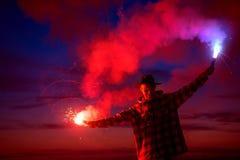 有信号火炬的人反对黑暗的日落天空 免版税库存照片