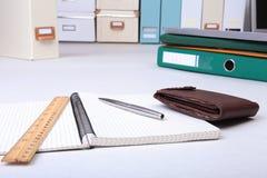 有信用卡、文件夹文件和笔记的皮革钱包关于书桌 被弄脏的背景 库存图片