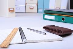 有信用卡、文件夹文件和笔记的皮革钱包关于书桌 被弄脏的背景 免版税库存照片