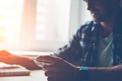 有信用卡、膝上型计算机和巧妙的手表的微笑的人 拟订dof重点现有量在线浅购物非常 免版税库存照片