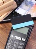 有信用卡、货币欧元,膝上型计算机和被包裹的箱子的付款终端在木板台 库存照片