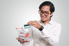 有信用卡和台车的愉快的亚裔人 免版税库存图片