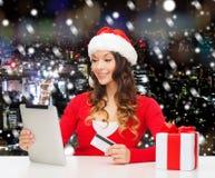 有信用卡和片剂个人计算机的微笑的妇女 免版税库存图片