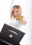 有信用卡和膝上型计算机的兴奋的少妇 图库摄影
