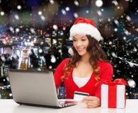 有信用卡和膝上型计算机的微笑的妇女 图库摄影