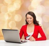 有信用卡和膝上型计算机的微笑的妇女 免版税图库摄影