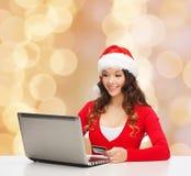 有信用卡和膝上型计算机的微笑的妇女 免版税库存照片
