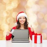有信用卡和膝上型计算机的微笑的妇女 库存图片