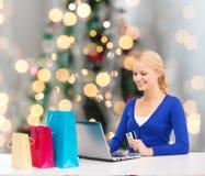 有信用卡和膝上型计算机的微笑的妇女 免版税库存图片