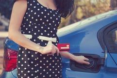 有信用卡开头汽车的汽油箱的妇女 免版税库存图片
