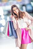 有信用卡的美丽的愉快的女孩和在shopp的购物袋 免版税图库摄影