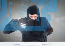 有信用卡的黑客使用在数字式屏幕后的一台膝上型计算机 库存照片
