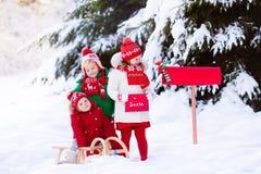 有信件的孩子给在圣诞节邮箱的圣诞老人在雪 免版税图库摄影
