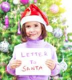 有信件的小女孩给圣诞老人 库存照片