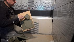 有修平刀的男性杂物工应用胶浆于瓦片的后部 影视素材