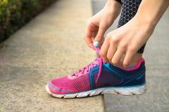 有修指甲的女性手栓在桃红色和蓝色运动鞋w的鞋带 免版税库存照片