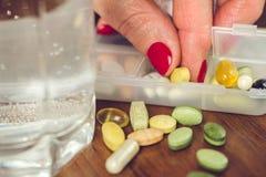 有修指甲的老女性手指采取从容器的药片有维生素和补充的混合的 免版税库存照片