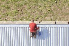 有修理屋顶的钻子的人 免版税库存照片