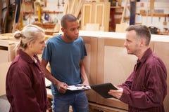有修造家具的学徒的木匠在车间 库存照片