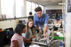有修造机器在科学机器人学方面或设计类的两位女性大学生的老师 免版税库存照片