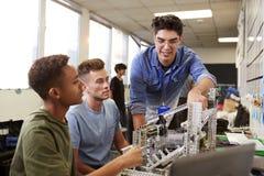 有修造机器在科学机器人学方面或设计类的两位男性大学生的老师 库存照片