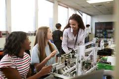 有修造机器在科学机器人学方面或设计类的女性大学生的妇女老师 库存图片