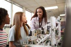 有修造机器在科学机器人学方面或设计类的女性大学生的妇女老师 免版税库存照片