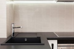 有修造的新的现代厨房在烤箱和镀铬物水龙头 库存照片