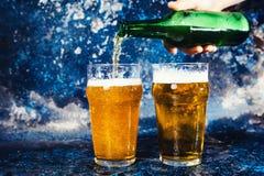 有倒草稿储藏啤酒的啤酒瓶的男服务员 库存照片