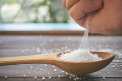 有倾吐的海盐的手在桌上的一把木匙子,侧视图 图库摄影