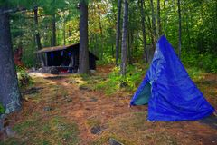 有倾斜对和一个篷布圆锥形帐蓬的原始Bushcraft露营地在Adirondack山脉原野 免版税图库摄影