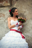 有倾斜对墙壁的婚礼花束的新娘 免版税库存图片