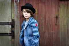 有倾斜对墙壁的帽子的男孩 免版税库存照片